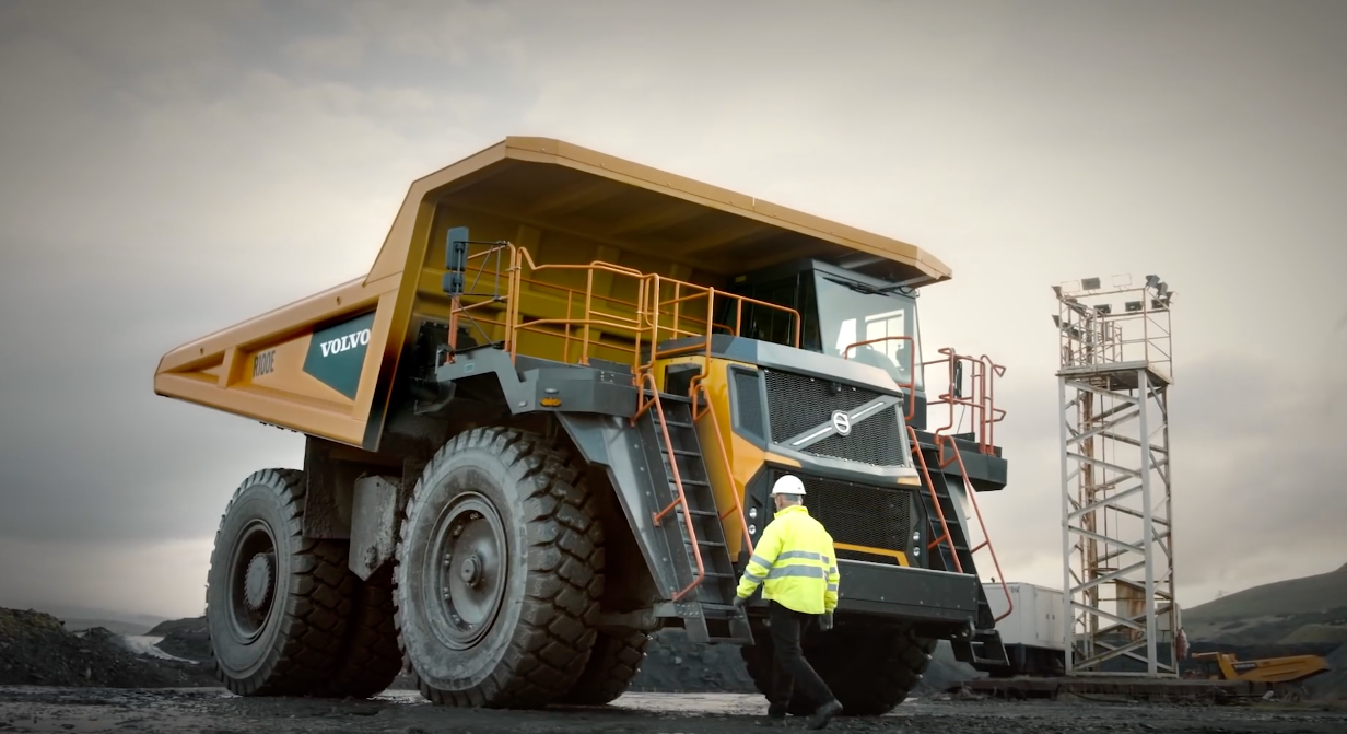 In a coal mining setting, a truck driver walks up to the enormous and imposing Volvo R100D rigid loader truck.