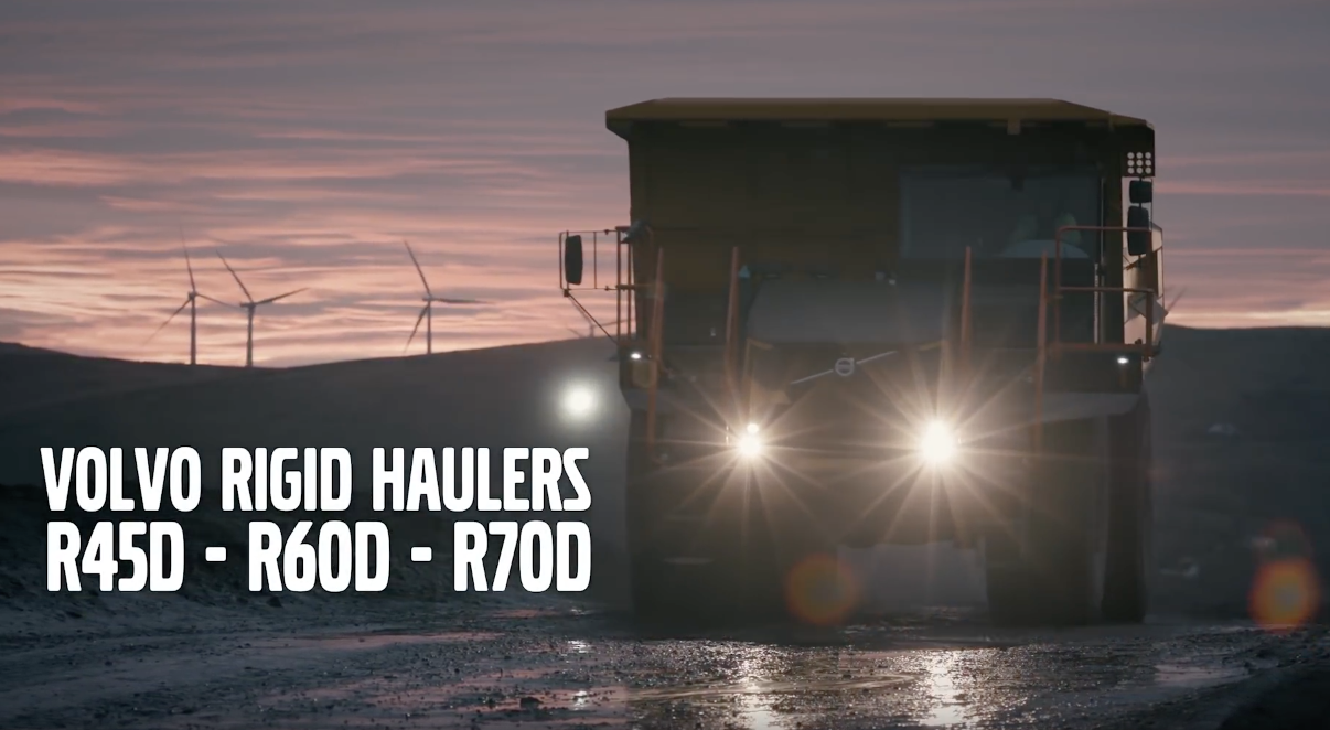 With headlights gleaming, the Volvo R60D drives along a muddy coal mine road at sunset.